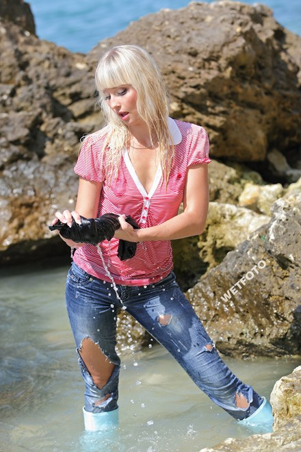 Wet Girl In Tight Jeans Sweater And Boots On Sea