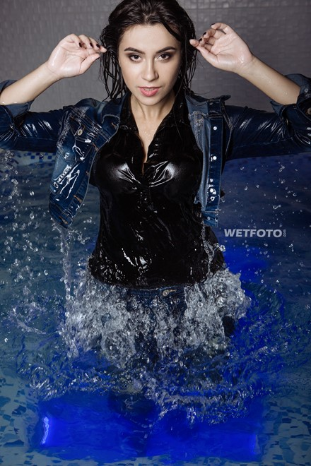wetlook girl with wet jeans clothing enjoying the water takes a shower swims in pool