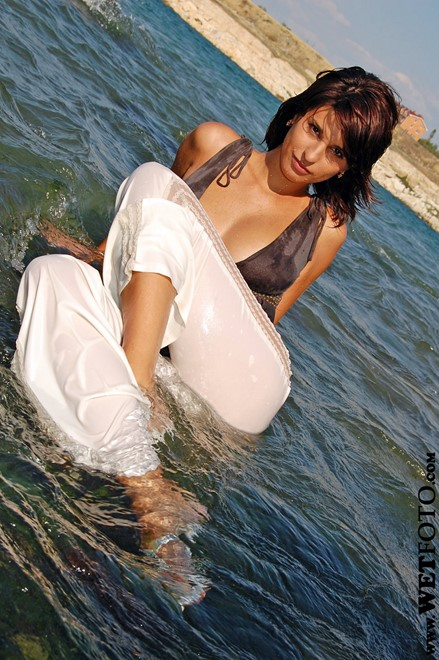 wet woman get wet wet hair fully clothed blouse pants sandals heels sea