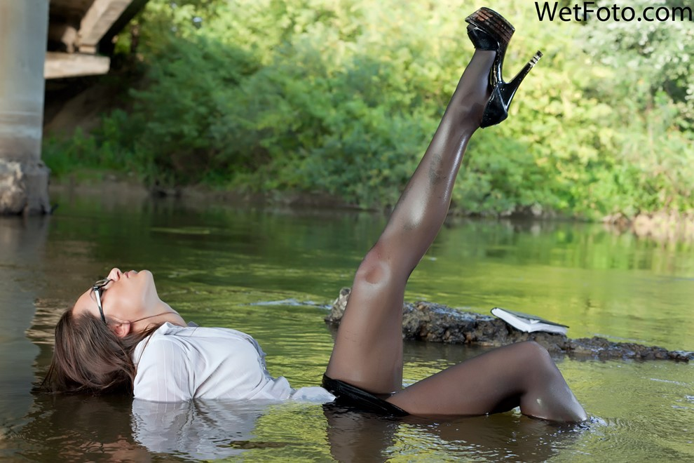 brunette wet woman get wet wet hair fully clothed shirt skirt stockings high heels glasses notebook river