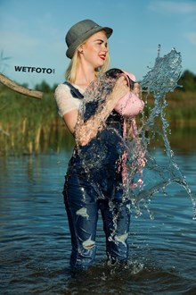 #415 - Joyful Blonde Girl in Jeans Jumpsuit, T-shirt, Hat and Shoes Get Wet on the Lake