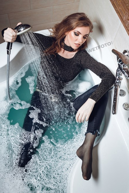 wetfoto beautiful girl takes bath shower fully clothed