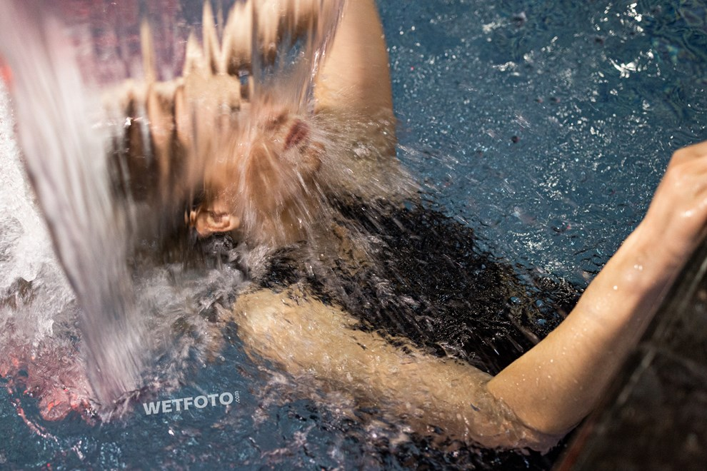 wetfoto woman swims pool fully clothed winter coat